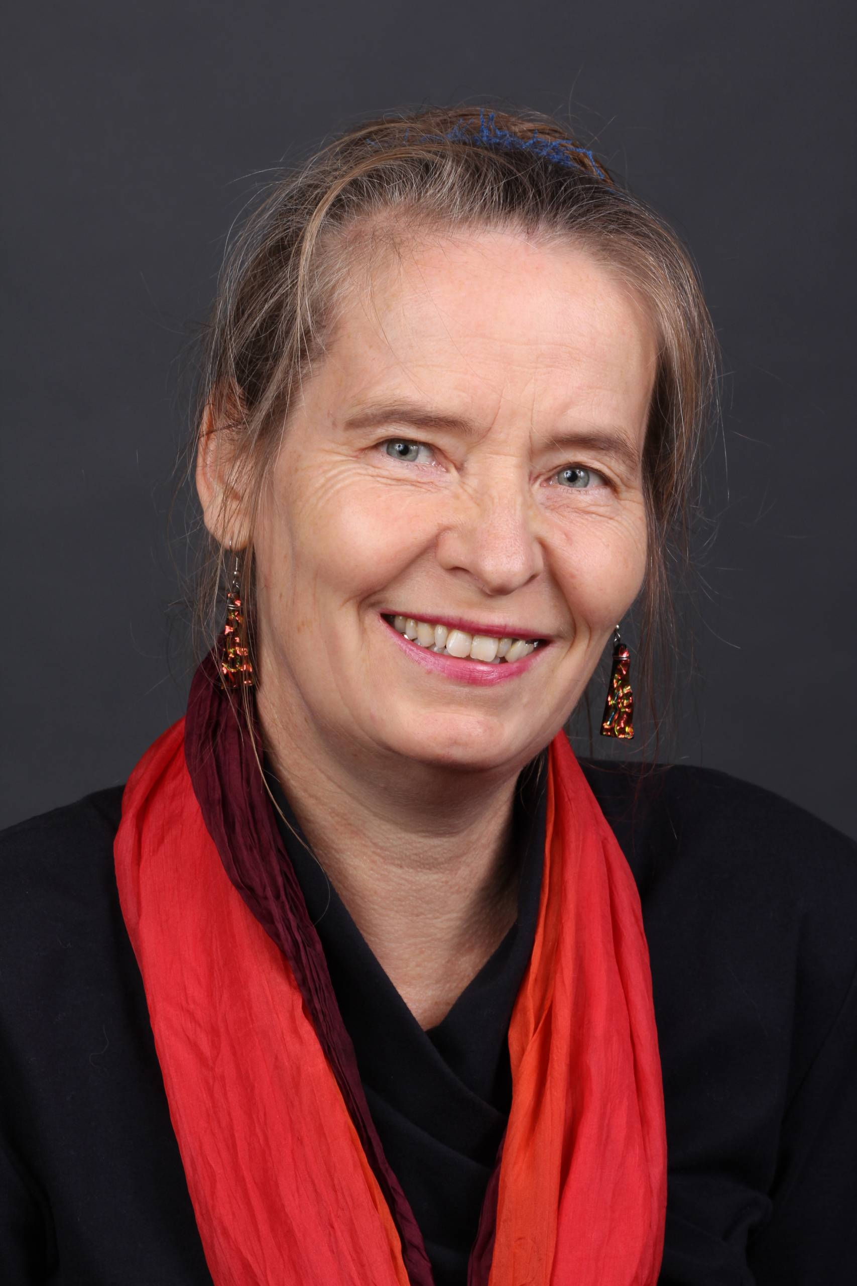 Headshot of Dorothee Ostmeier, woman wearing a black shirt and red scarf